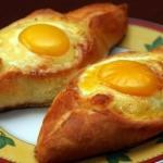 Хачапури по-аджарски едят вилкой, смешав в середине сыр, масло и яйцо и обмакивая в эту смесь отрезанные кусочки хрустящей лепешки.
